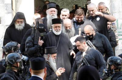 Fot. Security personnel escort Patriarch Portfirije and Bishop Joanikije